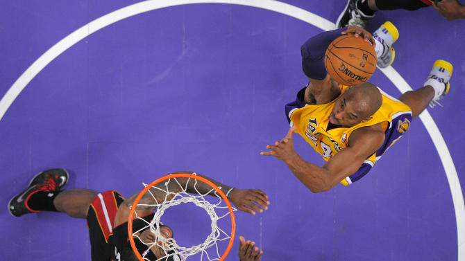 Los Angeles Lakers guard Kobe Bryant (24) goes up for a dunk as Miami Heat forward LeBron James (6) defends during the first half of their NBA basketball game, Thursday, Jan. 17, 2013, in Los Angeles. (AP Photo/Mark J. Terrill)