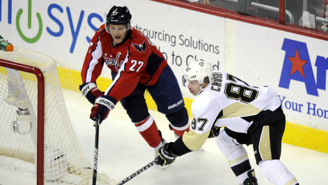 Pittsburgh Penguins center Sidney Crosby (87) tries to get the puck past Washington Capitals defenseman Karl Alzner (27) during the third period of an NHL hockey game on Thursday, Dec. 1, 2011, in Washington. (AP Photo/Nick Wass)