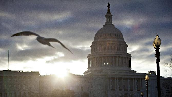 FILE - In this March 7, 2103 file photo, a seagull flies as the sun breaks through dark clouds at dawn over Capitol Hill in Washington. Members of Congress are traveling less and worrying more about meeting office salaries. Their aides are having to deal with longer lines and fewer prospects of a raise. Such are the indignities thrust upon the people who brought the country $85 billion in automatic government spending cuts this month. (AP Photo/J. Scott Applewhite, File)
