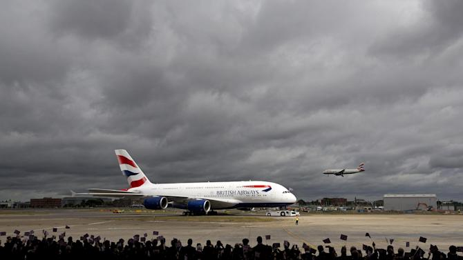 Airline staff wave flags at the arrival of a British Airways Airbus A380 at Heathrow Airport in London on July 4, 2013
