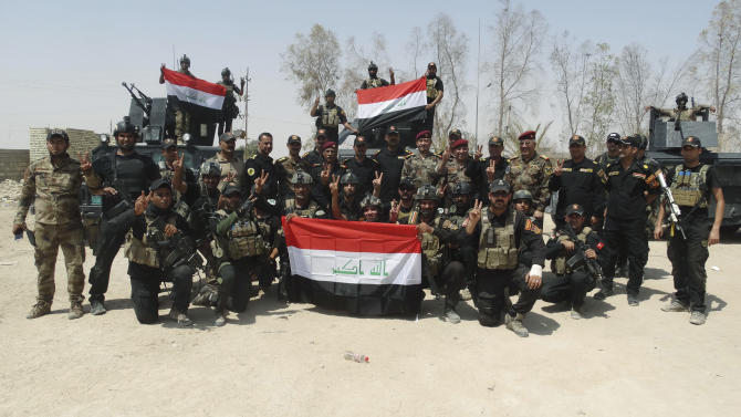 In this Tuesday, July 28, 2015 photo, Iraqi security forces with national flags pose for a photograph after regaining control of Anbar University in Ramadi, Iraq. Iraqi government forces backed by Shiite and Sunni pro-government fighters recaptured the university from the Islamic State militant group Sunday after hours of fierce clashes, provincial officials said, as part of its push to reclaim territory across the embattled province. (AP Photo)
