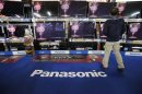 A man looks at Panasonic Corp's Viera TV screens displayed in an electronics store in Tokyo