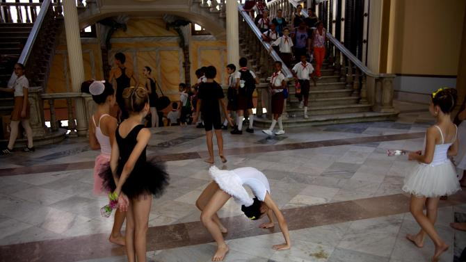 """In this April 3, 2013 photo, ballet students practice before a class at the National School of Ballet in Havana, Cuba. The school was founded seven decades ago by famed prima ballerina assoluta Alicia Alonso, now age 92, who is probably the most recognized person in Cuba not named """"Castro."""" (AP Photo/Ramon Espinosa)"""