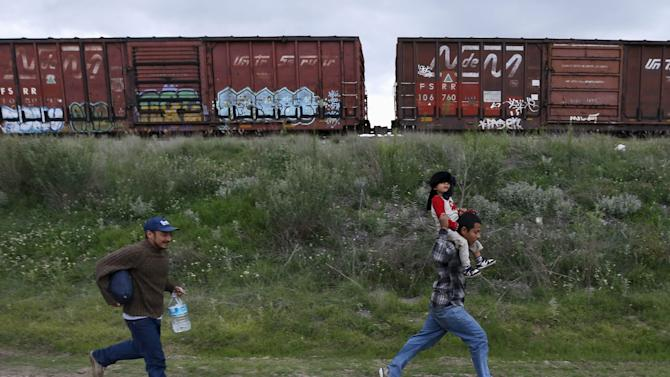 A Salvadoran father carries his son while running next to another immigrant as they try to board a train heading to the Mexican-U.S. border, in Huehuetoca