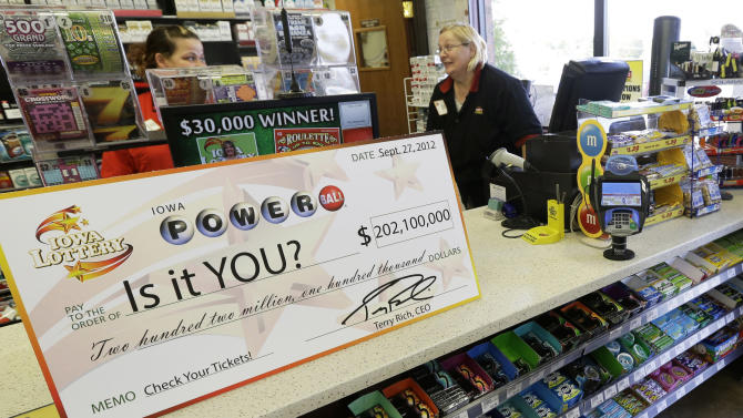 File - in this Sept. 27, 2012 file photo, a Powerball promotional check sits on the counter in the Casey's General Store, in Bondurant, Iowa. The jackpot for Powerball's Saturday, Nov. 24, 2012, drawing has climbed to $325 million, the fourth-largest in the game's history. (AP Photo/Charlie Neibergall, File)