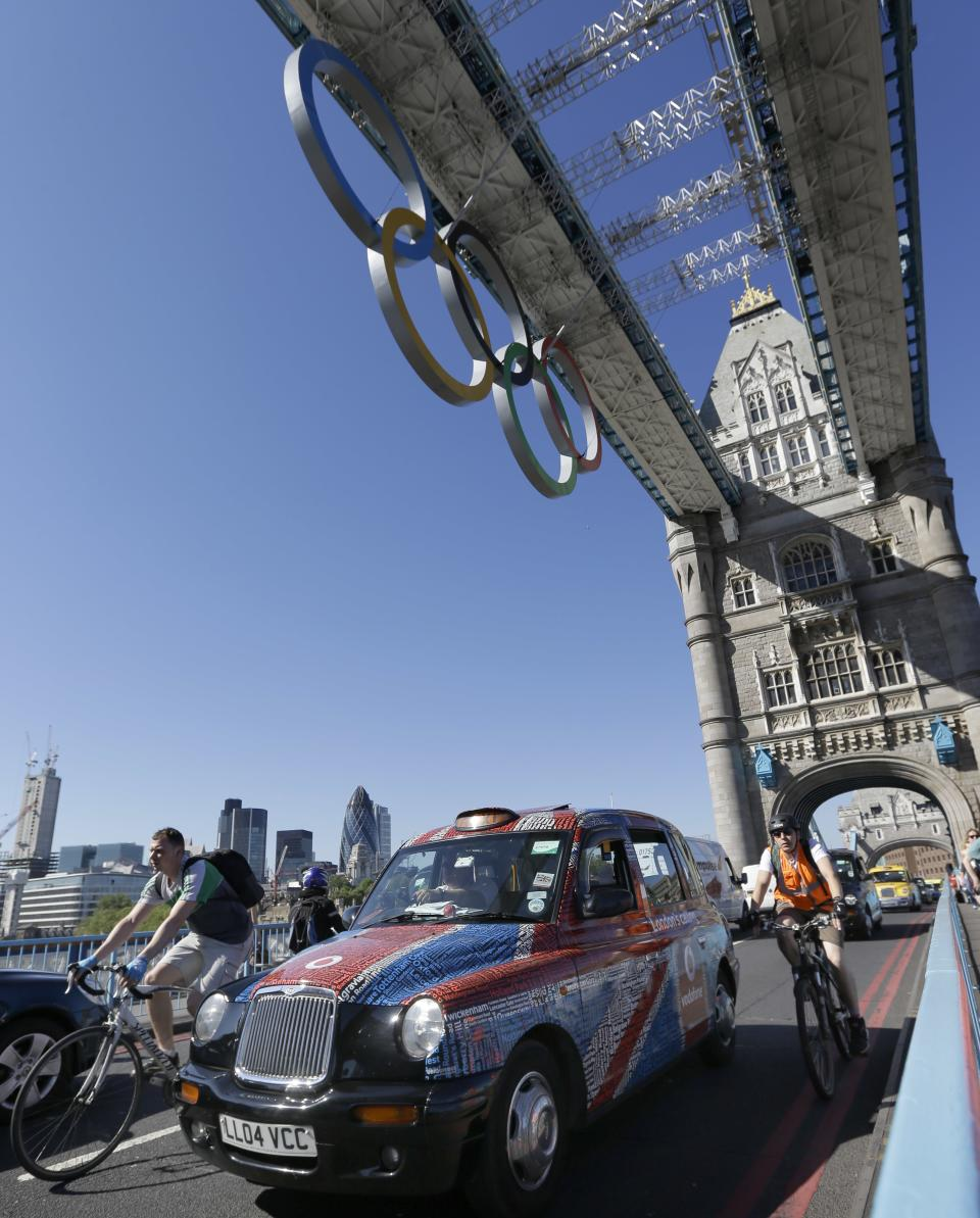 Taxis drive slowly in protest across Tower Bridge in London,  Monday, July 23, 2012. The traditional London taxis were holding a protest against not being allowed to drive in the Olympic Lanes once they come into force on Wednesday, July 25. (AP Photo/Kirsty Wigglesworth)
