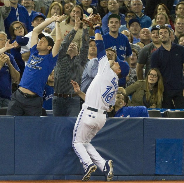 Blue Jays third baseman DeRosa reaches into the crowd to catch a foul ball during games against the Orioles in Toronto.