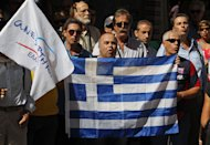 <p>               Supporters of the small right-wing Independent Greeks party, gathered outside the finance ministry before a meeting between Greece's finance minister and debt inspection teams from the International Monetary Fund, European Central Bank and European Commission, known as the troika, in Athens, Monday, Oct. 1, 2012. Greece's finance minister Yannis Stournaras will submit the 2013 draft budget to Parliament on Monday, as the government resumed negotiations with international creditors over a two-year additional austerity package. (AP Photo/Thanassis Stavrakis)