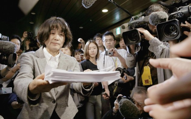 Bang Chung-Ja, co-chair of the Korean Council for Women Drafted for Military Sexual Slavery, hands over a protest petition to an Osaka City Hall official in Osaka