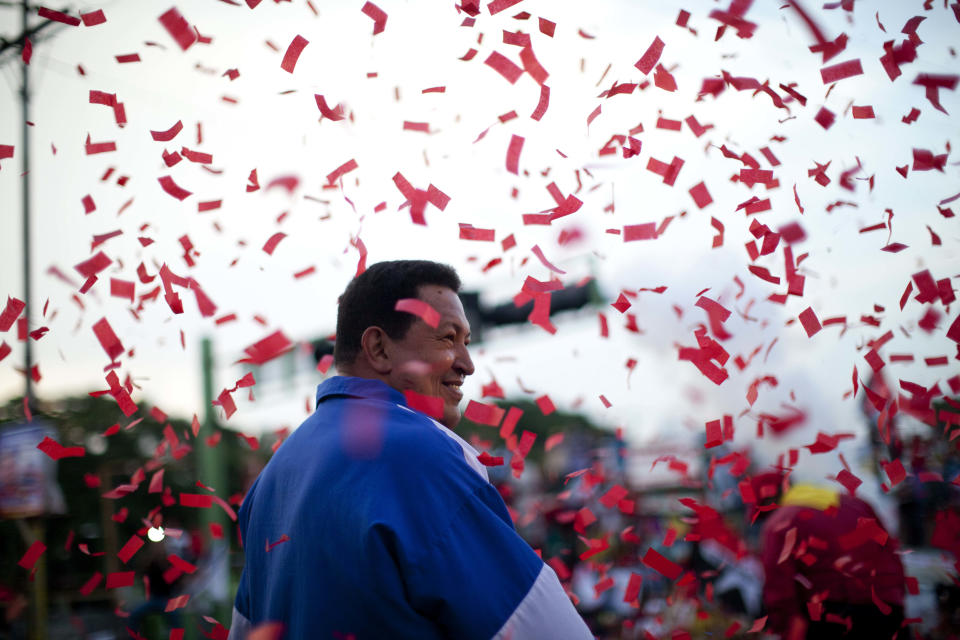 Under pouring confetti, Venezuela's President Hugo Chavez smiles during a campaign rally in Valencia, Venezuela, Wednesday, Oct. 3, 2012. Chavez is running for re-election against opposition candidate Henrique Capriles in presidential elections on Oct .7. (AP Photo/Rodrigo Abd)