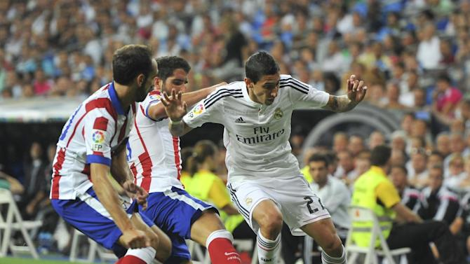 Real Madrid midfielder Angel di Maria (R) is challenged by two Atletico Madrid players during their Spanish SuperCup first leg at the Santiago Bernabeu stadium in Madrid, on August 19, 2014
