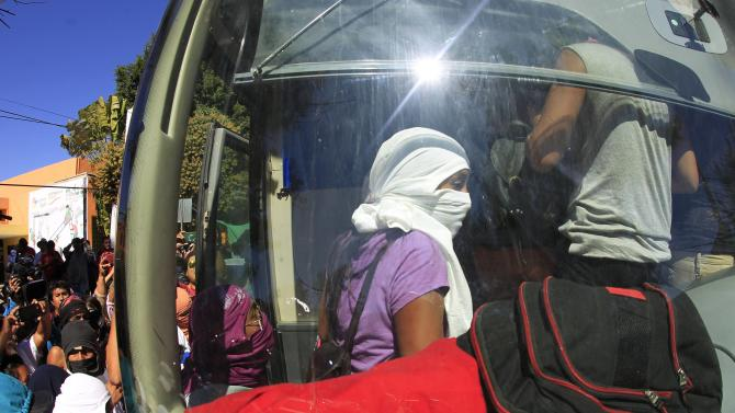 Members of the FUNPEG board a bus after members detained by federal police officers were released, at the Palo Blanco tollbooth on a road leading to Acapulco, in Chilpancingo