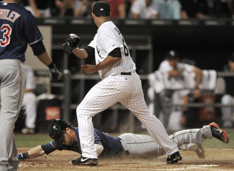 Cleveland Indians' Jason Kipnis slides into home plate safely as Chicago White Sox catcher Hector Gimenez tries to apply the tag during the first inning of the second game of a doubleheader baseball game in Chicago, Friday, June 28, 2013. (AP Photo/Paul Beaty)