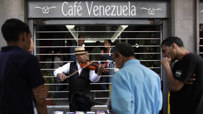 Musician Javier Munoz, 46, plays his instrument as he sells music outside of a cafe in Caracas, Venezuela, Tuesday, Feb. 19, 2013. Venezuela's President Hugo Chavez is back in Venezuela after 10 weeks of cancer treatment in Cuba, but he remained silent and out of sight on Tuesday, closed away in a tightly guarded military hospital, leaving the nation to speculate about whether he can still govern, and for how long. (AP Photo/Ariana Cubillos)