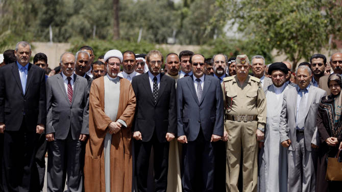 Iraqi Prime Minister Nouri al-Maliki, center right, Iraqi acting Defense Minister Sadun al-Dulaymi, center left, government officials, and parliament members, attend the funeral procession of five slain soldiers at the headquarters of the Iraqi Ministry of Defense in Baghdad, Iraq, Sunday, April 28, 2012. Gunmen killed 10 people in Iraq, including five soldiers near the main Sunni protest camp west of Baghdad on Saturday, the latest in a wave of violence that has raised fears the country faces a new round of sectarian bloodshed. (AP Photo/Hadi Mizban)