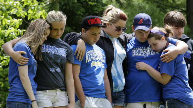 Brunswick High School students console each other at a crash site Monday, June 4, 2012, near Brunswick, Ohio. An 18-year-old boy died Monday, a day after he was thrown from a car just hours before his high school graduation in a northeast Ohio crash that killed three other teens. A car carrying Fox and four other teenagers went airborne, crashed, and flipped onto its roof at a railroad crossing early Sunday. (AP Photo/Tony Dejak)