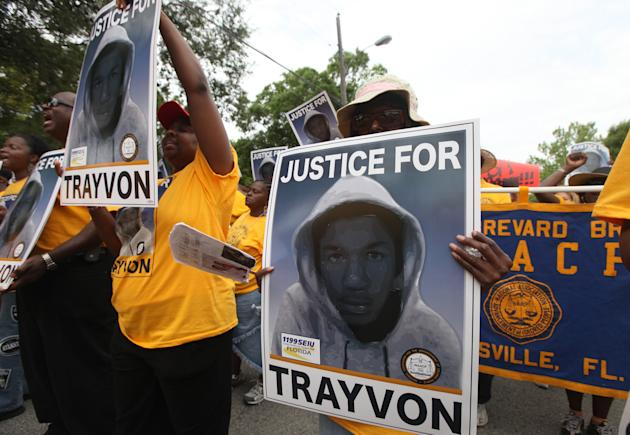 "Protestors hold up signs in a march and rally for slain Florida teenager Trayvon Martin on Saturday, March 31, 2012 in Sanford, Fla.  Protesters carried signs, chanted ""Justice for Trayvon,"" and clutc"