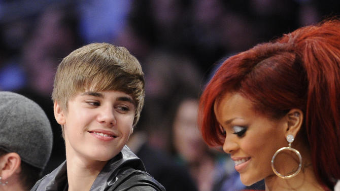Justin Bieber talks to Rihanna during the second half of the NBA basketball All-Star Game on Sunday, Feb. 20, 2011, in Los Angeles.  (AP Photo/Mark J. Terrill)