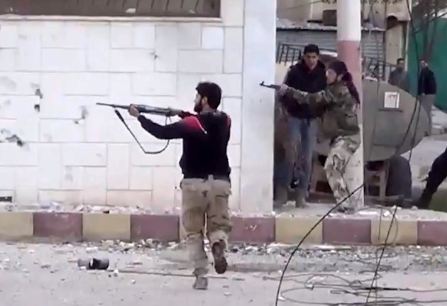 In this image taken from video obtained from the Shaam News Network, which has been authenticated based on its contents and other AP reporting, Free Syrian Army fighters fire at Syrian army soldiers d