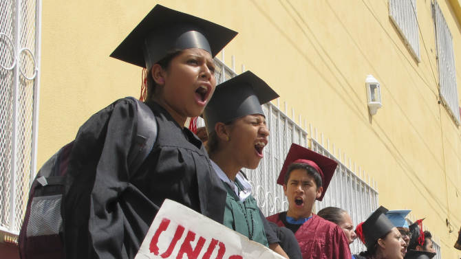 """Wearing graduation-style caps and gowns, Mexican youth raised in the U.S, chant slogans outside a migrant shelter before crossing the international bridge from Nuevo Laredo, Mexico, Monday Sept. 30, 2013. Wearing a colorful array of graduation-style caps and gowns, 34 young people who spent long stretches of their childhoods in U.S. cities like Phoenix and Boston chanted """"undocumented and unafraid"""" as they crossed the Rio Grande into Texas. (AP Photo/Christopher Sherman)"""