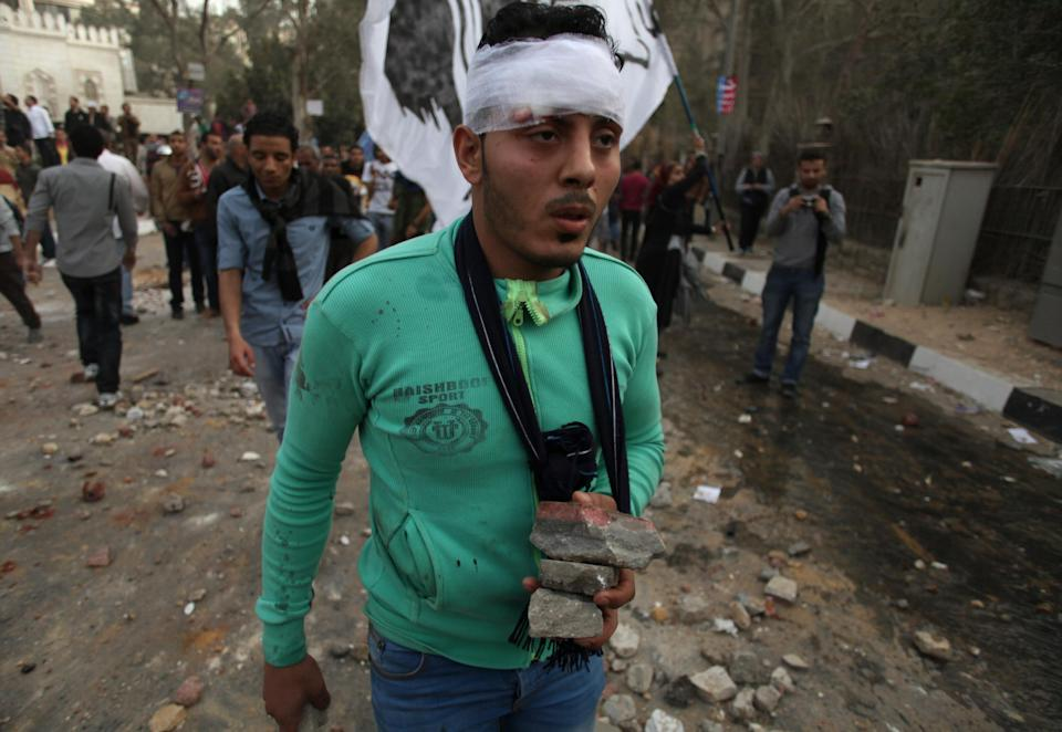 A wounded Egyptian protester carries stones during clashes between supporters and opponents and supporters of Egypt's powerful Muslim Brotherhood near the Islamist group's Cairo, Egypt headquarters Friday, March 22, 2013. (AP Photo/Khalil Hamra)