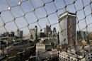 The City of London business district is seen through a wire fence in London