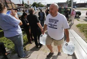 Canadian water activist McGuffin delivers containers of water from Canada to St. Peter's Episcopal church to protest against the increase in water shutoffs for residential customers with unpaid bills in Detroit