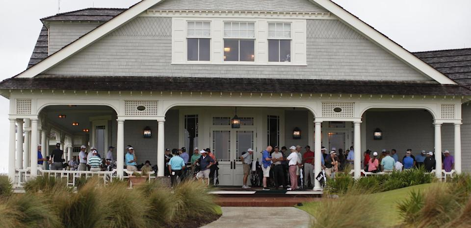 Golfers wait out the rain on the clubhouse porch during a weather-delayed practice round at the PGA Championship golf tournament on the Ocean Course of the Kiawah Island Golf Resort in Kiawah Island, S.C., Wednesday, Aug. 8, 2012. (AP Photo/Evan Vucci)
