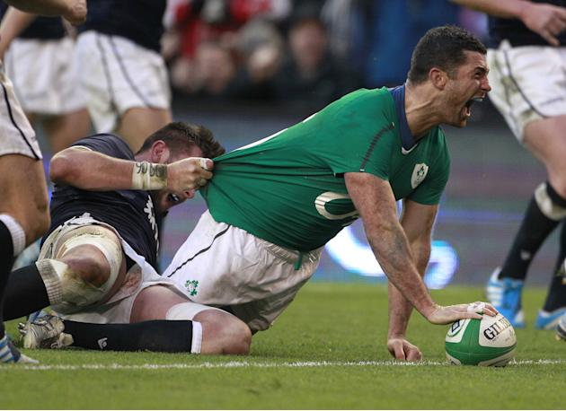 Ireland's Rob Kearney, right, celebrates after scoring a try despite being tackled by Scotland's Ryan Wilson during their Six Nations Rugby Union international match at the Aviva Stadium, Dubl
