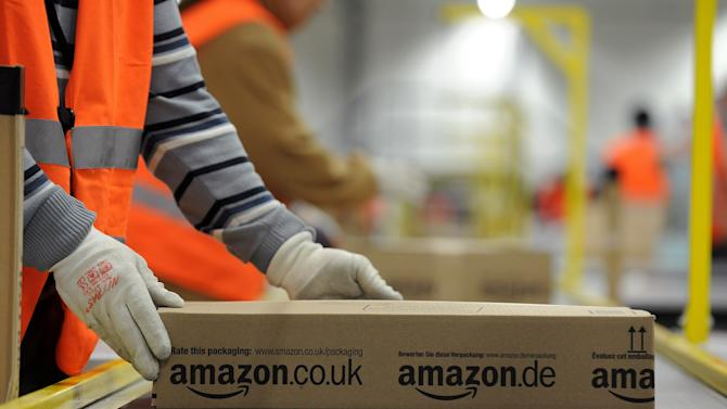 """FILE - In this Dec. 11, 2012 file photo an employee of Amazon works at the company's logistic center in Pforzheim, Germany. Online retailer Amazon reacted to mounting criticism Monday, Feb. 18, 2013, by firing a security company named in a German television documentary about alleged mistreatment of foreign temporary workers. An Amazon spokeswoman in Germany said the company had ended its relationship with Hensel European Security Services """"with immediate effect."""" (AP Photo/dpa, Jan-Philipp Strobel)"""