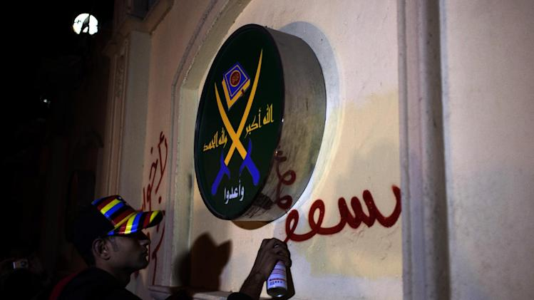 "FILE -- In this Sunday, March 17, 2013 file photo an Egyptian activist spray paints a slogan in Arabic that reads ""Brotherhood are sheep,"" next to a logo of the Muslim Brotherhood that reads in Arabic ""God is great, thank God, prepare,"" on the walls of the Brotherhood's headquarters during an anti Muslim Brotherhood protest, in Cairo, Egypt. Egyptians are closely following protests in Turkey, a country that has provided the heavily polarized and increasingly impoverished Egyptians with a tantalizing model for marrying Islamist government with a secular establishment and achieving prosperity along the way. Outside the Muslim Brotherhood, most Egyptians have been skeptical about the Brotherhood's analogy with the Turkish model and view it as a tactic to market itself in the West and assuage fears at home of strict Islamic rule. (AP Photo/Nasser Nasser, File)"