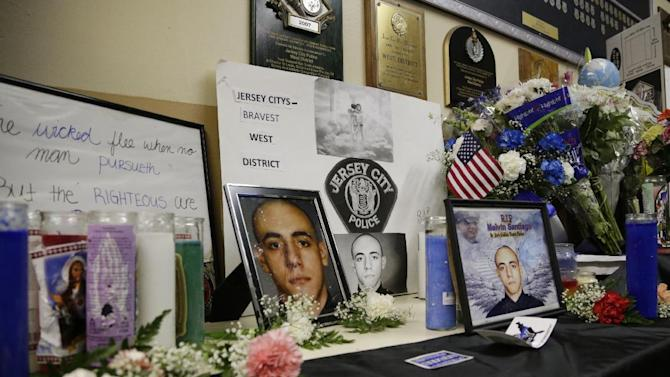 A makeshift memorial is seen for Jersey City Police officer Melvin Santiago, who was killed while on duty at the West District precinct, Tuesday, July 15, 2014, in Jersey City, N.J. Officer Santiago was shot in the head while still in his police vehicle as he and his partner responded to an armed robbery call at about 4.a.m., on Sunday, July 13. (AP Photo/Julio Cortez)