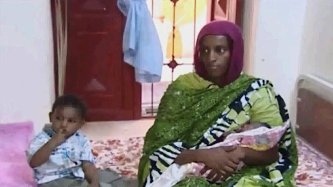 In this file image made from an undated video provided Thursday, June 5, 2014, by Al Fajer, a Sudanese nongovernmental organization, Meriam Ibrahim, sitting next to Martin, her 18-month-old son, holds her newborn baby girl that she gave birth to in jail last week, as the NGO visits her in a room at a prison in Khartoum, Sudan. Sudan's official news agency, SUNA, said the Court of Cassation in Khartoum on Monday, June 23, canceled the death sentence against 27-year-old Meriam Ibrahim after defense lawyers presented their case. The court ordered her release. (AP Photo/Al Fajer, File)