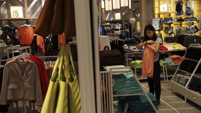 A Lefties employee folds clothes at a Lefties store in Madrid