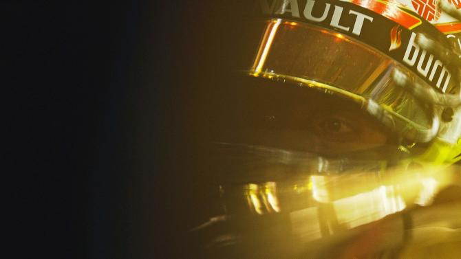 Lotus Formula One driver Maldonado of Venezuela looks on from his car in the garage during the first practice session of the Singapore F1 Grand Prix