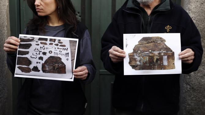 Forensic expert Etxeberria and archaeologist Garcia Rubio hold pictures showing the remains of niches, one of them appeared with the letters M.C. on it,  found in the crypt of Trinitarian convent in Madrid