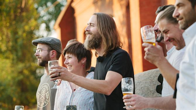 In this Saturday, July 19, 2014, photo provided by Stone Brewing Co., Stone Brewing Co. CEO and Co-founder Greg Koch, center, toasts the crowd after announcing the Escondido, Calif., brewery's plan to build a brewery and bistro in Berlin. Stone Brewing Co. is spending about $25 million to renovate a historic gas works building into a brewery, packaging and distribution center, restaurant and garden set to open late next year. Stone Brewing Co., one of the top 10 biggest craft breweries in the U.S., will make beer for its bistro and distribution throughout Germany and Europe. (AP Photo/Stone Brewing Co., Frederik Ferschke)