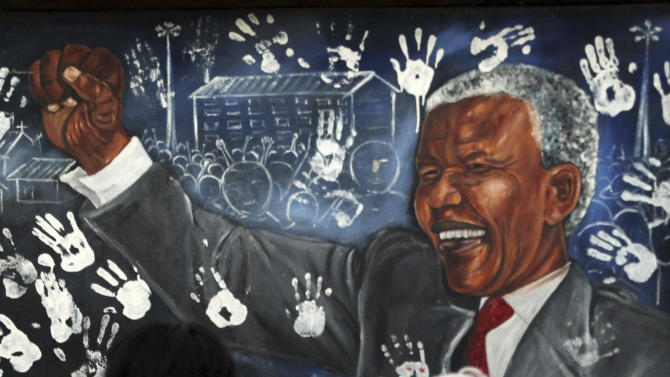 Two women walk past a mural depicting former South African President Nelson Mandela at the Alexandra township in Johannesburg, South Africa, Tuesday, July 17, 2012, designed to honor Mandela's 94th birthday which is celebrated Wednesday, July 18. (AP Photo/Themba Hadebe)
