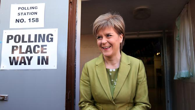 First Minister of Scotland and Scottish National Party leader Nicola Sturgeon smiles as she poses for photographers after casting her ballot in the general election at Broomhouse Community Hall in Broomhouse, Scotland, Britain, Thursday, May 7, 2015. (AP Photo/Scott Heppell)