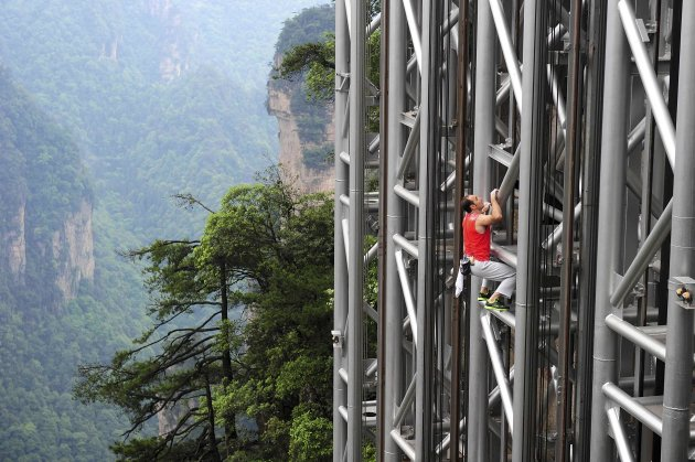 France's daredevil climber Casanova climbs the Bailong Elevator near a cliff in Zhangjiajie