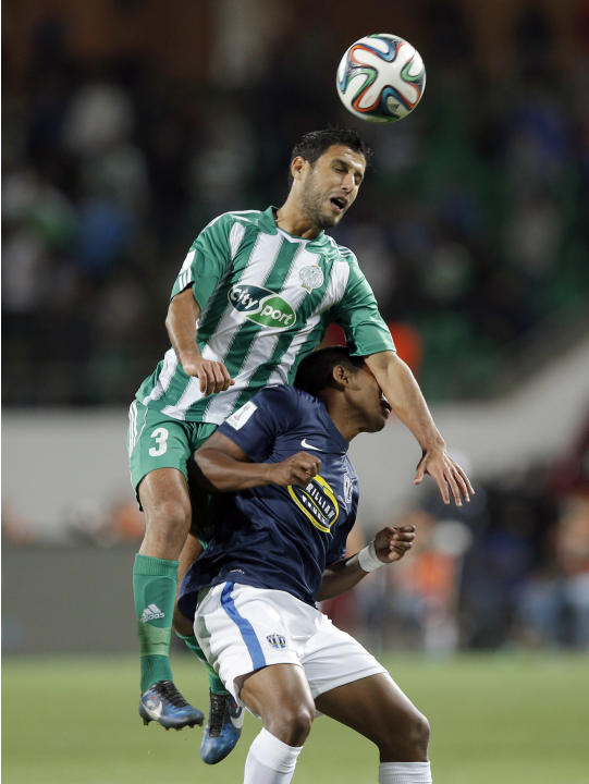 Raja Casablanca's Zakaria El Hachimi, left, and Auckland City FC's  Roy Krishna jump for the ball during the opening game of the FIFA Club World Cup soccer tournament in Agadir, Morocco, Wedne