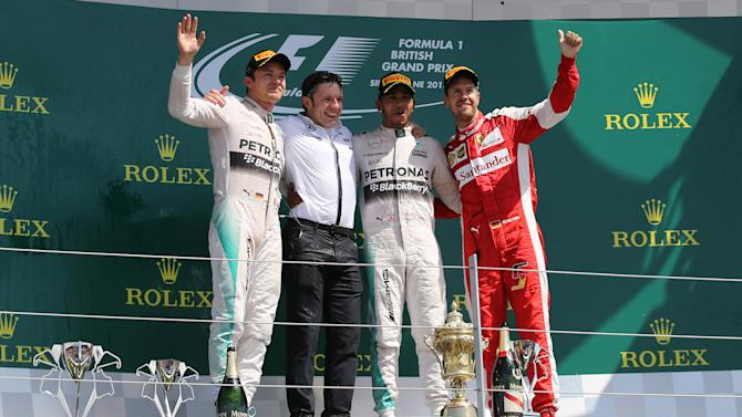 CAR: Mercedes' Lewis Hamilton celebrates his win on the podium with Nico Rosberg of Mercedes (L) Ferrari's Sebastian Vettel (R) and Mercedes race engineer Peter Bonnington