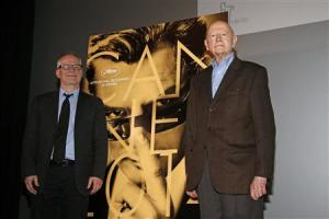 Cannes Film festival general delegate Fremaux and its director Jacob pose near this year's poster to announce the competing films at the 67th Cannes Film Festival in Paris