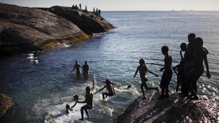 In this Feb. 6, 2012 photo, people jump into the water from Arpoador beach in Rio de Janeiro, Brazil. Rio is a city of contrasts, where vastly different worlds rub shoulders, and the unexpected lies lurking around every corner. (AP Photo/Felipe Dana)