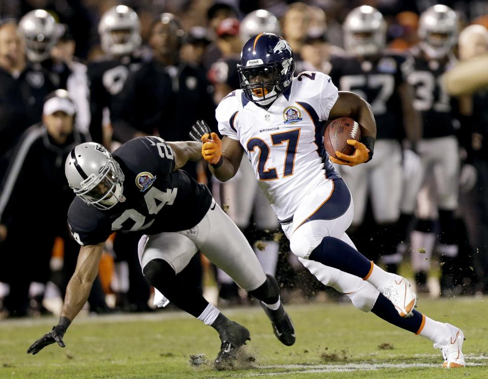 Denver Broncos running back Knowshon Moreno (27) carries the ball past Oakland Raiders cornerback Michael Huff (24) during the first quarter of an NFL football game in Oakland, Calif., Thursday, Dec. 6, 2012. (AP Photo/Marcio Jose Sanchez)