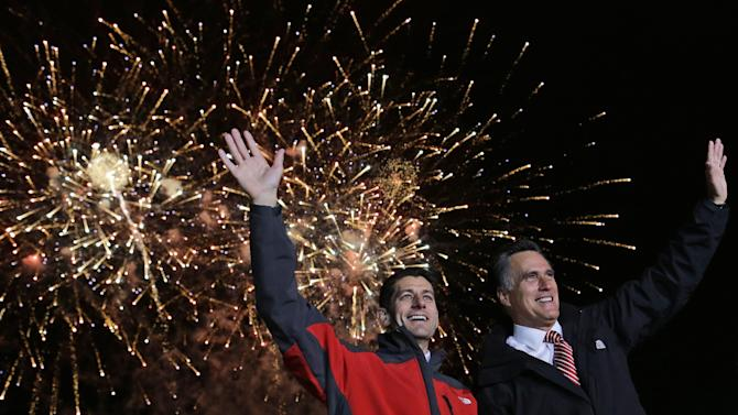 Republican presidential candidate and former Massachusetts Gov. Mitt Romney, right, and his vice presidential running mate, Rep. Paul Ryan, R-Wis., wave as fireworks go off at a campaign event at the baseball field of North Canton Hoover High School in North Canton, Ohio, Friday, Oct. 26, 2012. (AP Photo/Charles Dharapak)