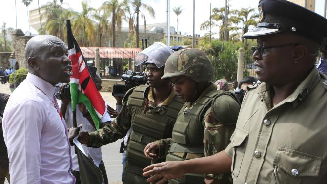 Police stop a protester from demonstrating outside Kenya's parliament in the capital Nairobi