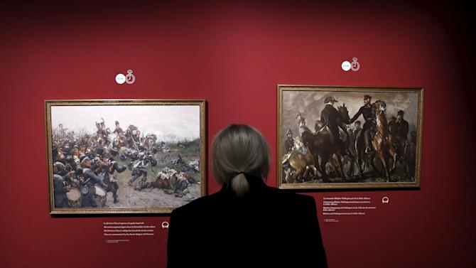 """A man looks at paintings depicting the Battle of Waterloo at the museum """"Memorial 1815"""" in Braine-l'Alleud"""
