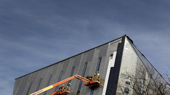 In this Feb. 15, 2012 photo, people work on the side of the new Cleveland Museum of Contemporary Art in Cleveland. The building is expected to be done and open to the public in the Fall of 2012. The Commerce Department reported Monday, April 2, 2012, that construction spending fell 1.1 percent in February after a drop of 0.8 percent in January which was revised down from an initial estimate of a decline of 0.1 percent. (AP Photo/Amy Sancetta)