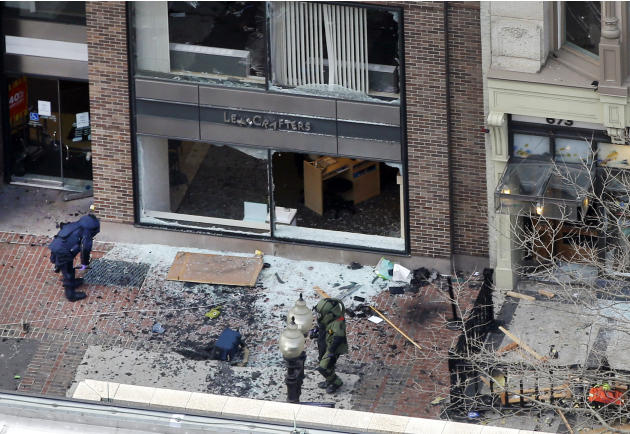 One of the blast sites on Boylston Street near the finish line of the 2013 Boston Marathon is investigated by two people in protective suits in the wake of two blasts in Boston Monday, April 15, 2013.